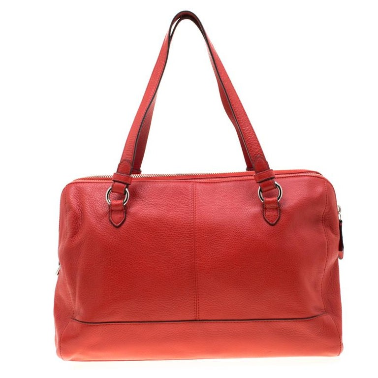 A versatile accessory, you can use this luxurious red leather bag for multiple occasions. The smooth satin interior comes with three zip compartments for you to house your essentials in an organized manner. Coach is known for its perfection in