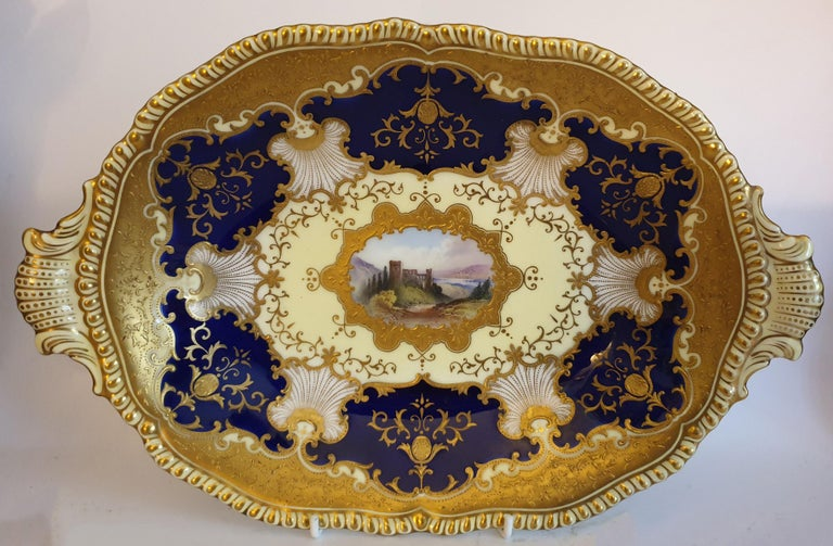 A Coalport Porcelain eight-piece dessert service,comprising a set of six dessert plates, an oval two handled serving dish and a square two handled serving dish, each with a hand painted central cartouche; 'Loch Aw', 'Heilige*', 'Godstow Bridge',