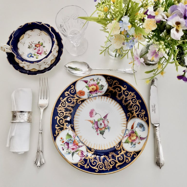 This is a very beautiful plate made by John Rose in Coalport in circa 1805 or 1810, which was the Georgian era. The plate has a beautiful cobalt blue ground, rich gilding and elegant hand painted floral reserves.  Coalport was one of the leading