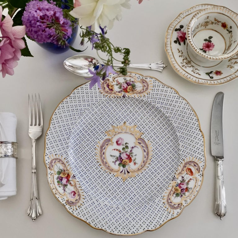This is a wonderful Coalport dinner plate made in circa 1820, which is known as the Regency period. The plate has moulding all-over the surface, as well as gilded reserves with beautiful hand painted flowers.  Coalport was one of the leading