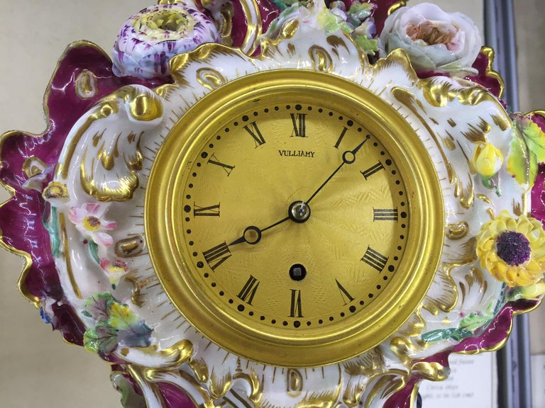 A fine early 19th century Coalport Porcelain cased timepiece by this famous maker.  The elaborate pink ground porcelain case is set with exotic birds and flowers on scroll feet, with gilded scrollwork and latticework. The 2.75 inch gilt dial with