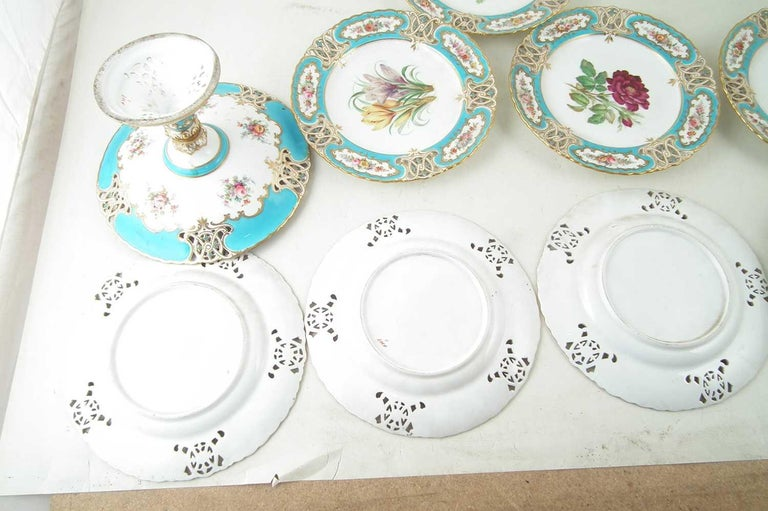 Minton reticulated exceptional botanical turquoise dessert service for 8 with comport. Reticulated in the shape of royal arms each plate individually hand painted with a different floral specimen to the center with reticulated turquoise enameled