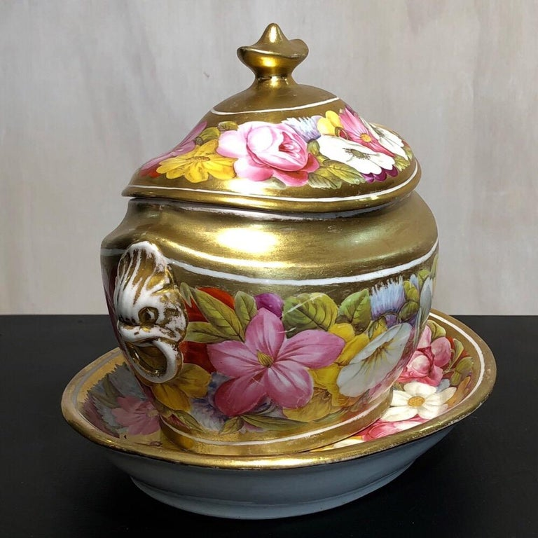 John Rose Coalport sucrier and a matching teapot stand, lavishly decorated with colorful flowers on a gold ground. Decorated in the Baxter studio.