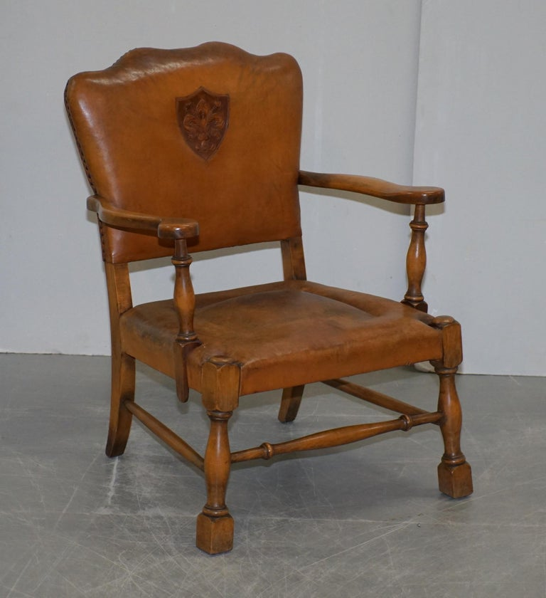 We are delighted to offer for sale this lovely pair of Edwardian smart club armchairs with oak frames and brown leather upholstery that have embossed coat of arms armorial crests in the back