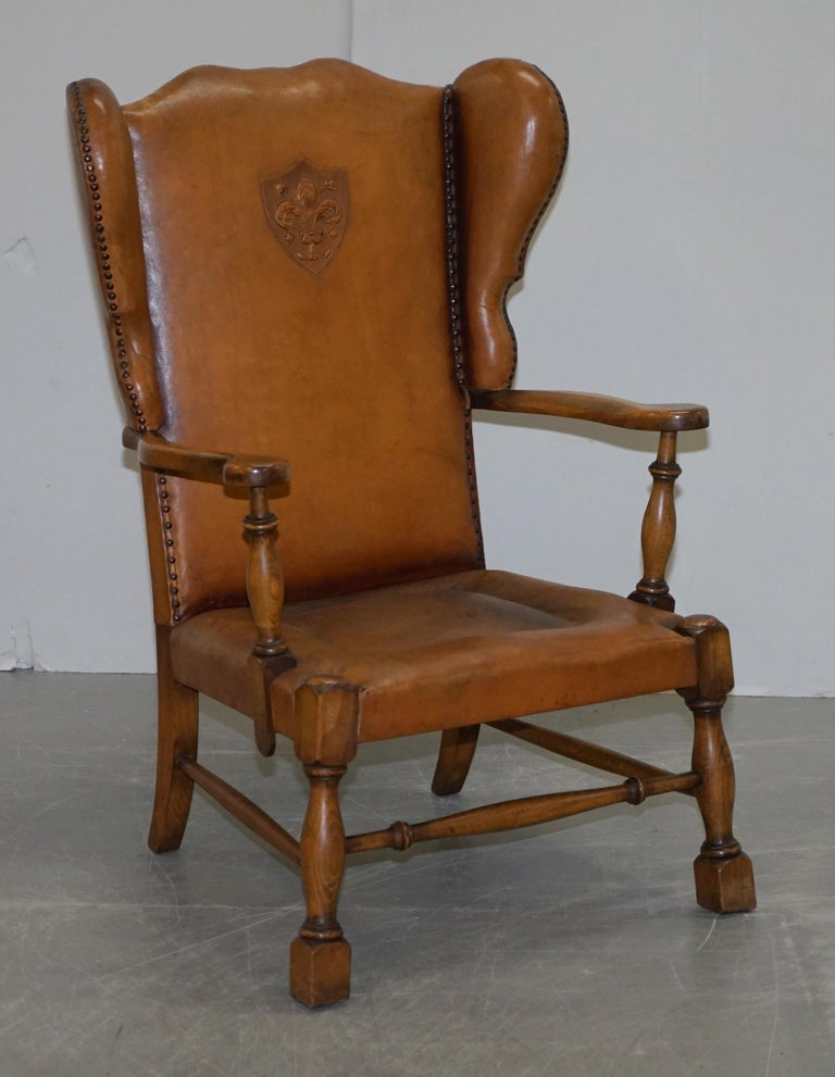 We are delighted to offer for sale this lovely pair of Edwardian wingback armchairs with oak frames and brown leather upholstery that have embossed coat of arms armorial crests in the back