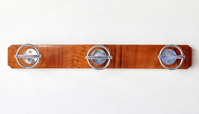 Designed by that most French of French designers, Jean Royère, and made in the 1960s, this coat rack is a fruitwood-veneered wooden plank fitted with three nickel-plated brass patères (