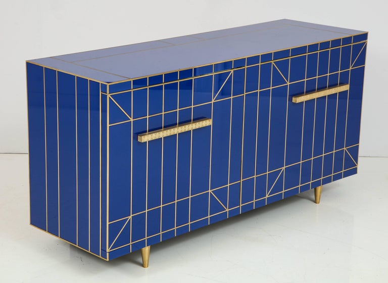 Elegant and timeless cobalt blue glass sideboard or credenza with tapered brass legs and brass inlays. Interior is lined in mirror. Two doors open to reveal a large storage area separated by a smaller top level shelf that is clad in mirror. This is