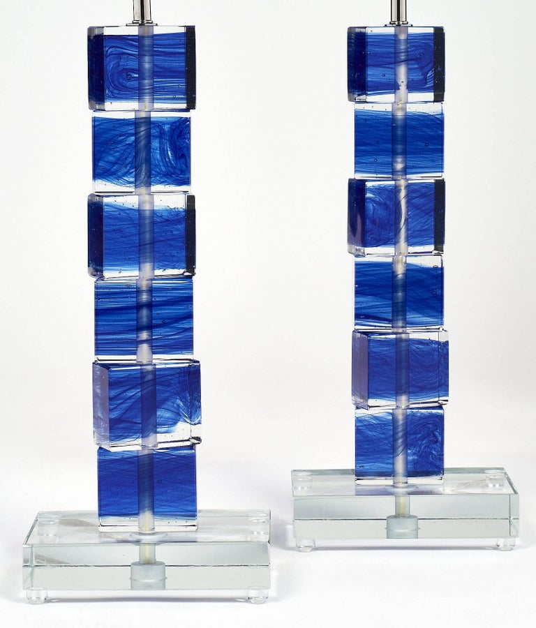 Unique pair of Murano glass cobalt blue lamps. Each features stacked clear glass cubic elements with blue color fused in the blocks. They sit on a clear glass base. These lamps have been newly wired to fit US standards.