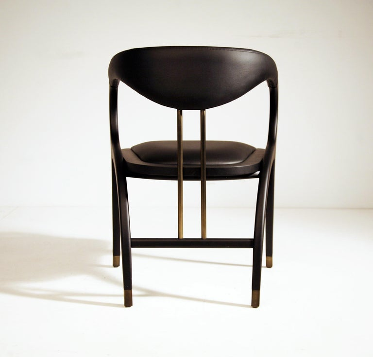 The Cobra chair features extraordinary design with curved back legs that form part of the armrests and back support in a continuous silhouette. Handcrafted of solid oak in ebony finish and bronzed metal. Upholstered seat and backrest in genuine