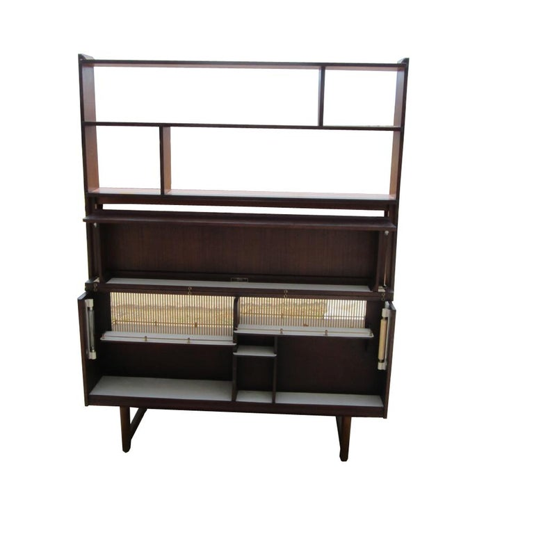A Mid-Century Modern display cabinet or bar with a credenza. This cocktail cabinet has a detachable display top, two drawers, two cabinets and a back that opens to a mini-bar. Comes with lighting fixtures in the bar section. When completely closed