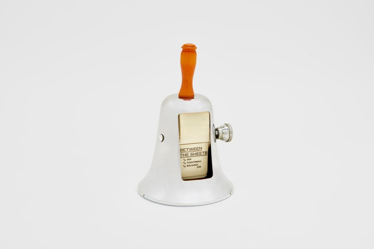 A chrome-plated and bakelite, ivorine cocktail recipe menu in the shape of a bell. This stunning Art Deco piece is the perfect addition to any home or professional bar. The nob on the side of the piece turns each separate hand coloured ivorine (a