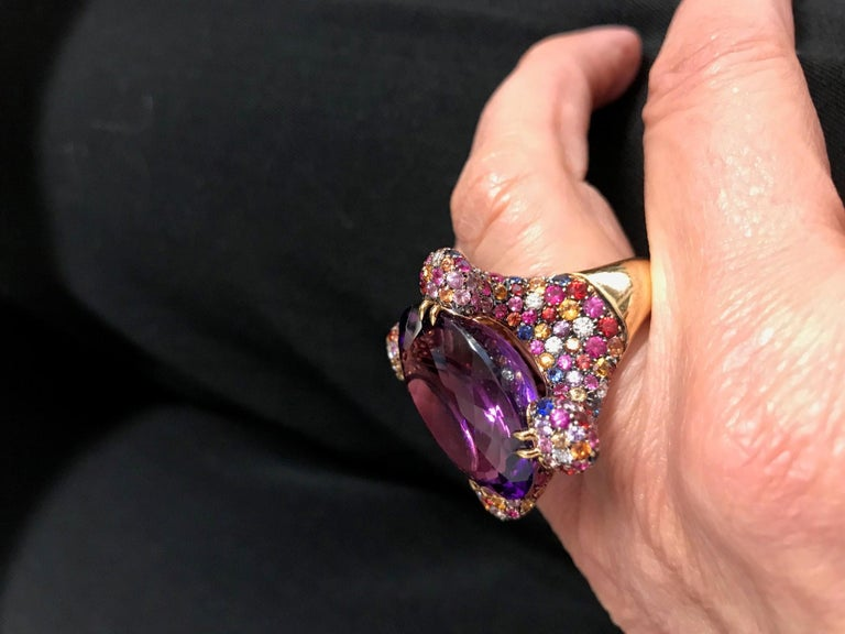 Handcrafted in Margherita Burgener family workshop, based in Valenza,  Italy, in 18kt rose gold, the colorful cocktail ring is centering the February birthstone amethyst.    Brasilian Natural Amethyst  33.40 carats. 244 sapphires, from pink, blue,