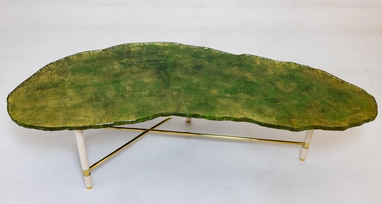 A rare find. This table with original Brass and painted wood base, was produced by Fontana Arte around 1953 in Italy. The table features a free form glass top with a chipped edge. The glass has been painted by Dulio Barnabe under the name Dubè. Dubè