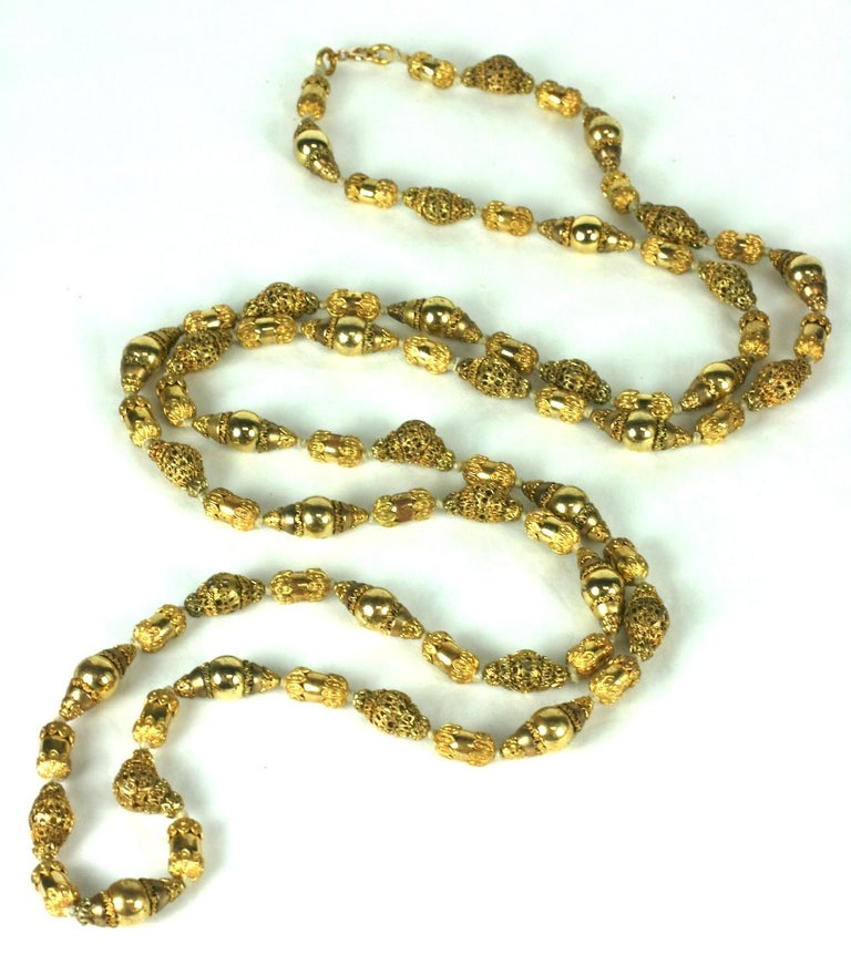 Coco Chanel Gilt Filigree Bead Long Necklace, Goossens. Long chain with gilt filigrees stacked and layered with polished gilt beads. A subtle play on matte and shiny in a long, transformable hand knotted bead necklace. 56