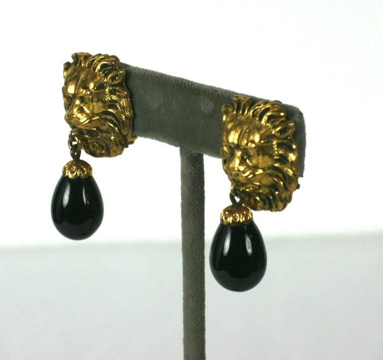 The most classic, early earrings from Coco Chanel with lion heads' motifs . One of her favorite codes in textured and gilded bronze. Black Pate de verre pendant teardrops with clip back fittings.  France circa 1960s.   Unsigned.  Excellent