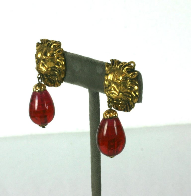 The most classic of earrings from Chanel with lions heads motifs . This is one of her favorite code motifs in textured and gilded bronze. Ruby Pate de verre pendant teardrops with clip back fittings. France circa 1960s.  Unsigned. Excellent