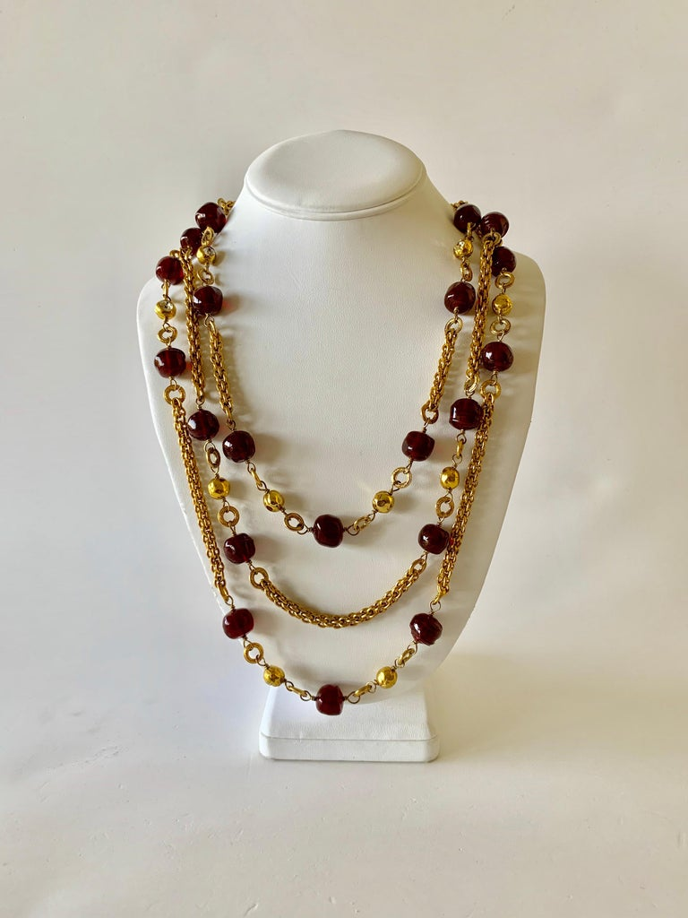 Beautiful vintage Coco Chanel triple strand cranberry statement necklace - by the famous Parisian Ateliers of Robert Goossens and Maison Gripoix. The necklace is comprised out of three strands of classic French rope chain with a combination of rich,