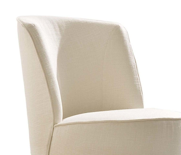 True to its name, this stunning armchair has an enveloping and welcoming shape atop a sleek swivel round base made of polished steel that makes it the ultimate sophisticated accent in a modern decor. Upholstered in ivory fabric (col. 1240/01 cat.