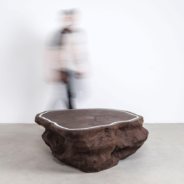 Composed in a language of landscape-oriented abstraction, the made-to-order coffee table is cast from entirely in coffee grounds. A humorous and striking combination, the organic, textural mass contrasts the slick, cement-inlaid top.