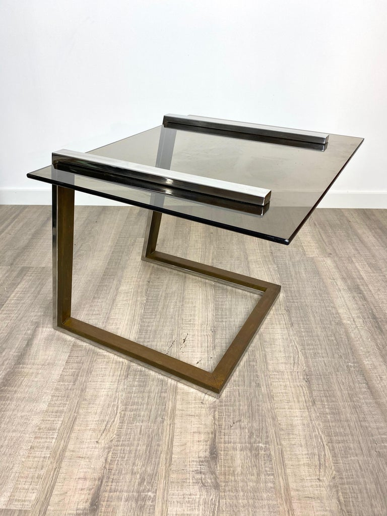 Coffee side table in the style of the Italian designer Romeo Rega in a chrome and brass structure and smoked glass surface. Italy, circa 1970.