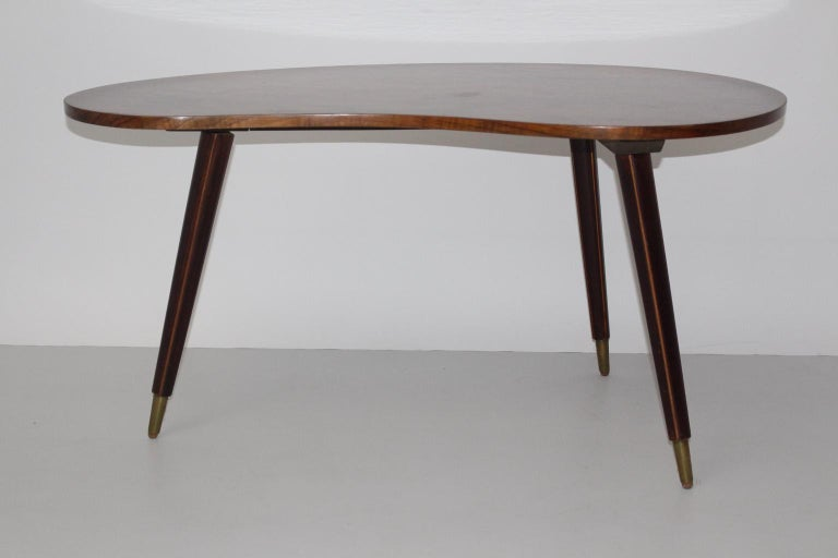 This coffee table bean-shaped was designed and made in Vienna, circa 1950. The top of the coffee table was made of pressboard and walnut veneered. The legs, which were made of solid walnut, show a maple-tree inlay and brass sabots.  approx.