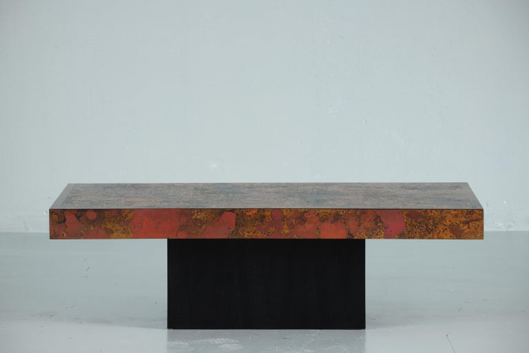 Beautifully oxidized copper tabletop with acid resting on a lacquered wooden base.