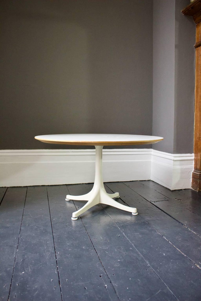Simple and elegant coffee table designed by George Nelson in the 1960s for Herman Miller.  This model has a white laminate top - with nicely chamfered edge revealing plywood layers below - on white enameled four-star base. Manufactured in the UK