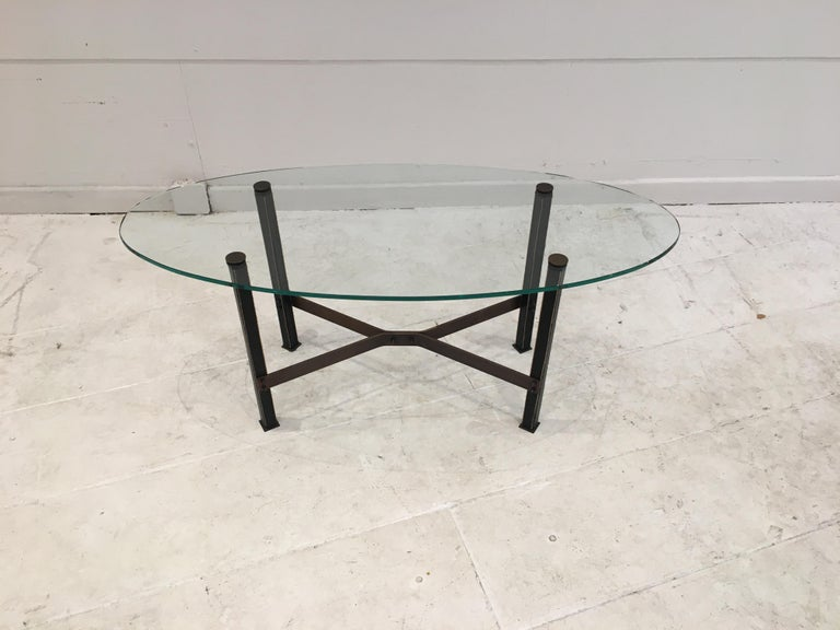 Model Canasta by Mathieu Matégot, circa 1960. Coffee table with four square section legs covered in black leather with saddle stitching. Brass cruciform spacer and oval shaped new glass top.