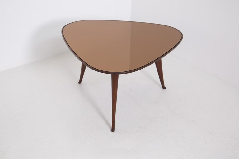 Elegant coffee table by Osvaldo Borsani from the 1950s. The coffee table is made of walnut wood with a triangular shape. Its three supporting legs have slightly curled feet at the bottom. The table top is made of dark orange mirrored glass,