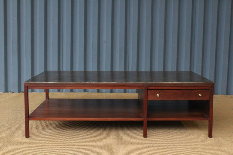 Mahogany coffee table designed by Paul McCobb for Calvin Furniture, 1950s. Features brass trim around the original leather top. Two drawers with brass pulls. Recently refinished. Leather surface shows a few minor signs of wear.