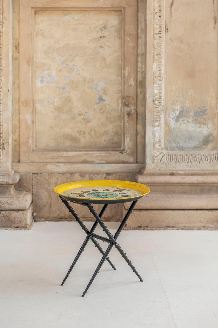 Brilliant yellow coffee table attributed to Fornasetti. Yellow and multicolor top tray with the iconic dirigible and hot-air balloons theme. The below structure is a dark wood decorated stool with original silk and brass details.