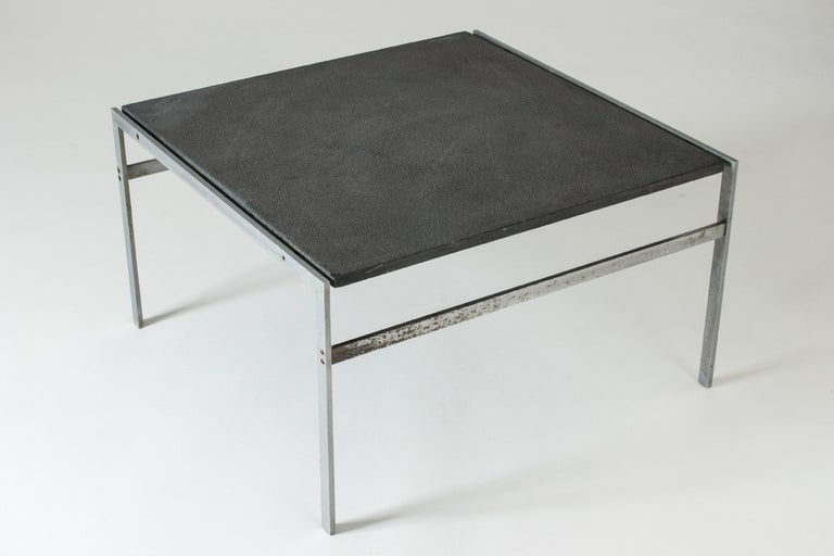 Cool coffee table by Preben Fabricius & Jørgen Kastholm, made from a crisply cut steel frame and a grey, structured stone tabletop.