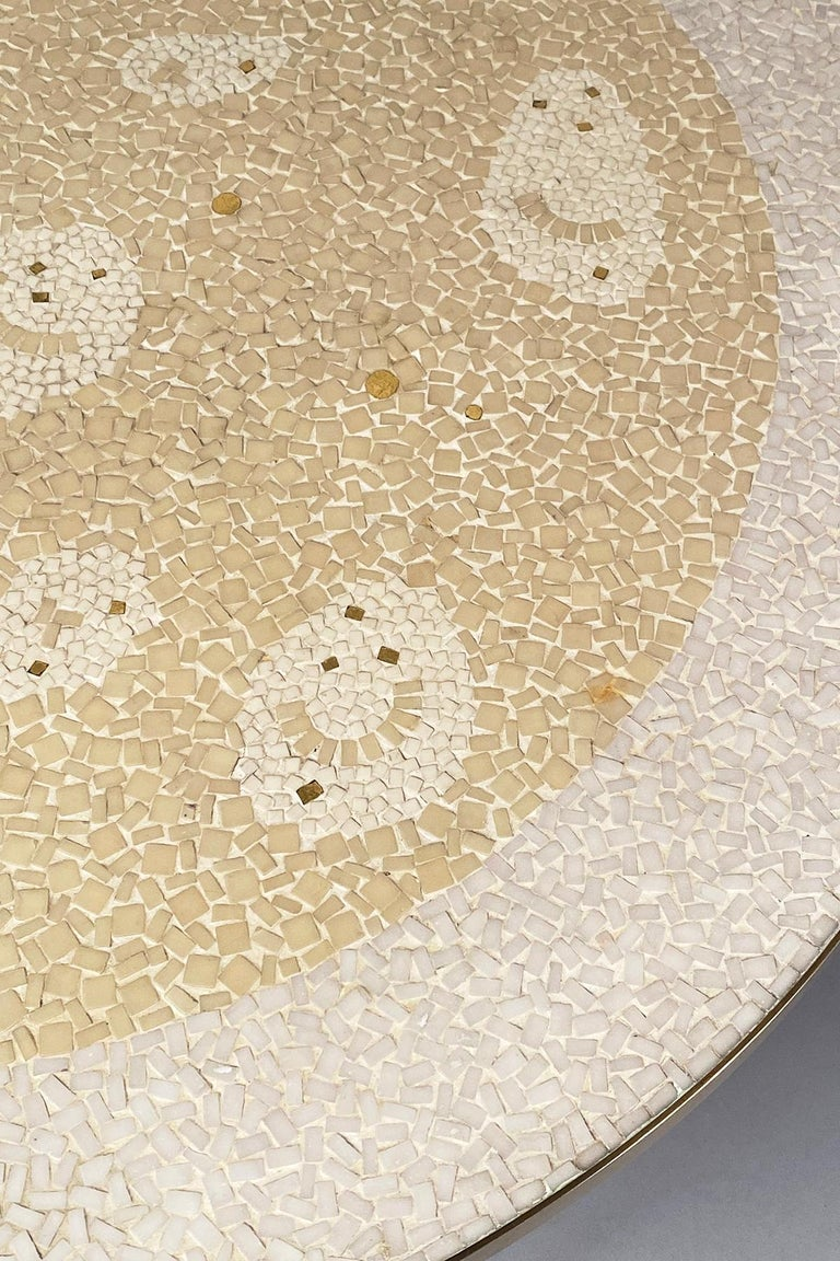 White and beige mosaic top with gold highlights, raised on a brass base with hairpin legs.