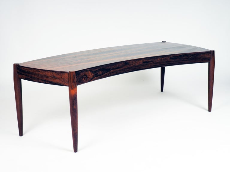 Coffee table in bent shape. Made in rosewood by Trensum, Sweden. The table was designed by the Danish architect Johannes Andersen.