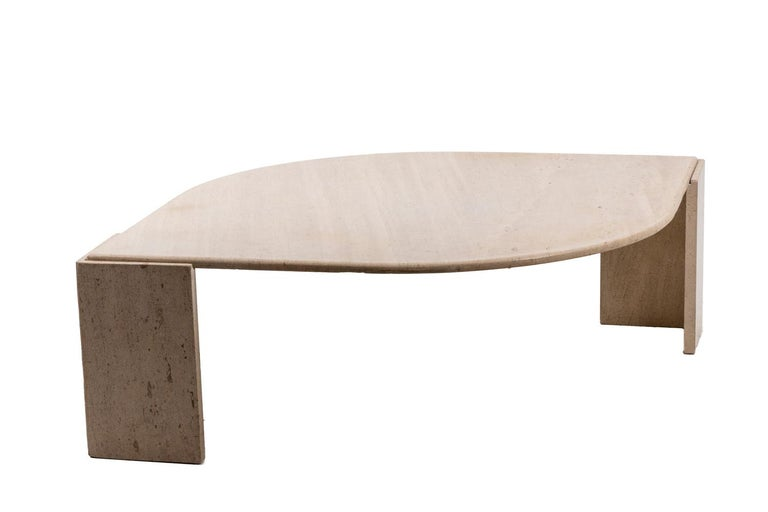 Travertine coffee table in the shape of an eye. The top comes to rest on two L shaped grooved legs.  Work realized in the 1970s.