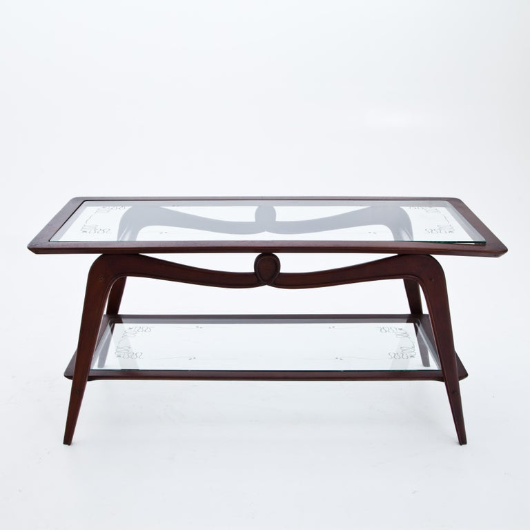 Rectangular coffee table with two glass shelves with etched decorations and a wooden curved frame.