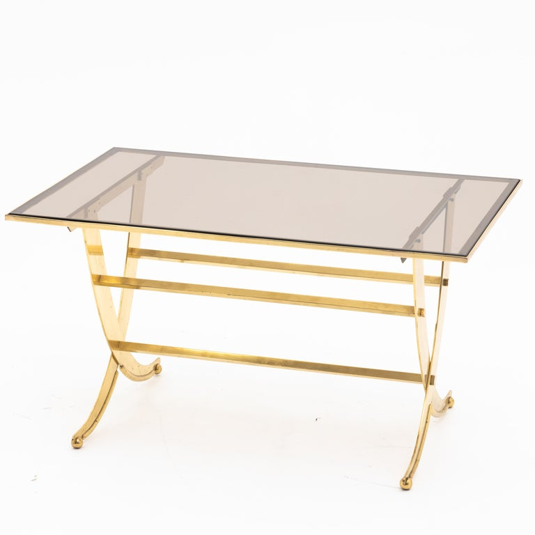 Coffee table standing on X-shaped brass frame with rectangular smoked glass top.
