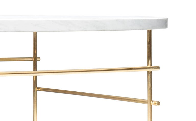 Coffee table is a Minimalist low table composed of a circular top made of treated Carrara marble and four brass legs joined together with cross-bars welded with silver.