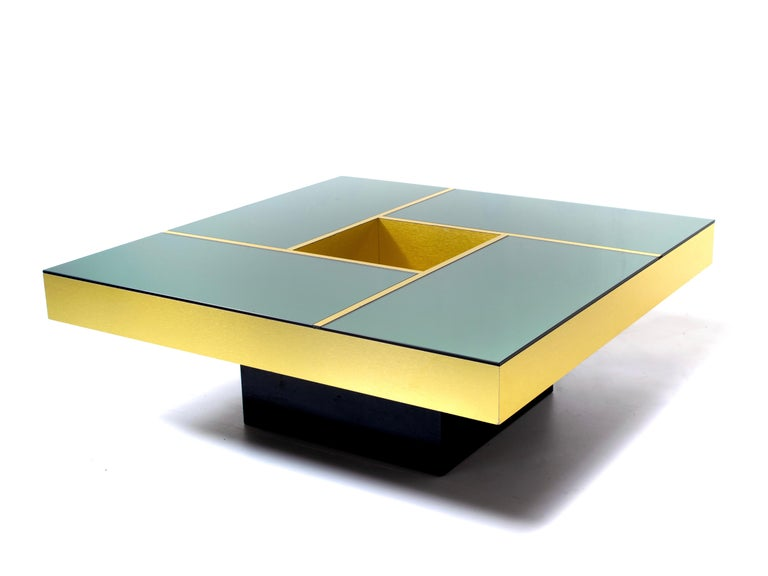 Coffee table 'Shilling' designed by Giovanni Ausenda, Guido Baldo Grossi & Gianni Gavioli for NY Form of Bologna in the 1970s. Amazing gold colored table with a smoked mirror top that is divided into four sections divided by gold bands. This table