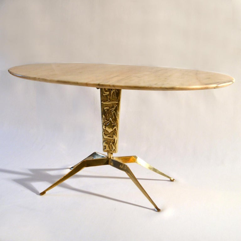 Oval coffeetable with pink cream top with black veins supported by a sculpted cast brass base with a relief of figures and four spider legs on oval feet. The figures on the leg are abstracted in a typical 1950s style and tell the story of