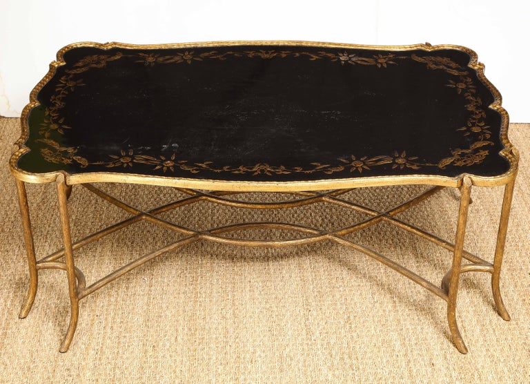 This table is oozing with personality! The top is lacquered wood with a chinoiserie style painted design within a scalloped gilt metal frame. On gilt metal legs. Its shape and mix of materials make it a statement piece in any room.