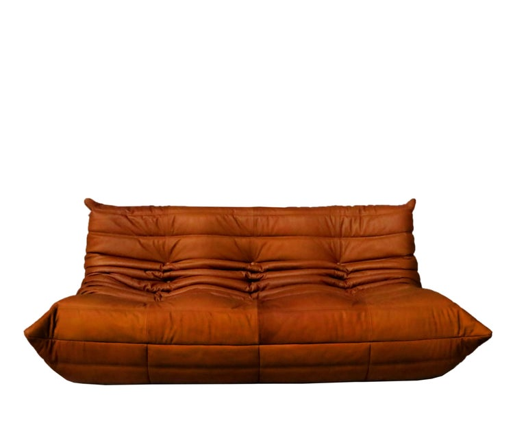 We are famous for our top quality leather and our excellent togo Ligne Roset upholstering specialty. 1 three-seat 1 two-seat 1 single seat 1 pouf 1 corner pieces.  Iconic French sofa set. Wonderful full grain cognac leather edition. Designed 1973,