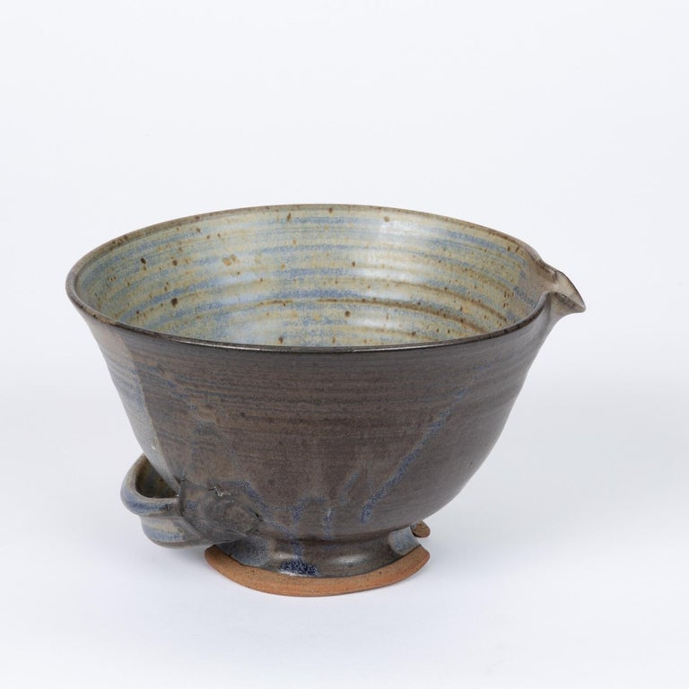 Colander style Studio Pottery stoneware bowl with a striated glaze, featuring soft blue tones throughout. The piece features a unique hand-formed low handle, opposing spout and drainage holes on the bottom.
