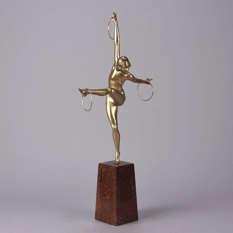 An energetic Art Deco cold painted bronze figure of a naked dancer balancing a set of three rings on her hands and outstretched foot. The surface of the bronze with good deep golden colour, the figure raised on a shaped marble base the top of which
