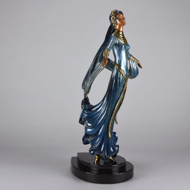 A fabulous limited edition Art Deco bronze of a beautiful young woman in elegant dress with vivid enamel colour highlighted with gilt bronze plaited headband and belt. The figure raised on an integral stepped plinth. Signed Erté, dated 1989,