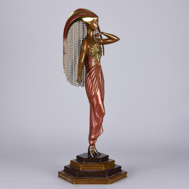 A fabulous limited edition Art Deco bronze of a beautiful young woman in diaphanous dress cold painted with enamel color and with bright gilded highlights wearing a spectacular headdress representing the sun of circular form with hanging appendages.