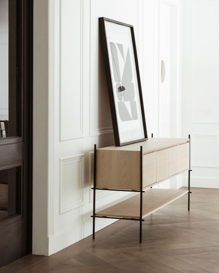 The Credenza Colima follows the concepts of functionalism with its two shelf surfaces and storage area. The electrostatic painted steel structure shows its pure essence, and the wood veneer brings warmth to the piece.