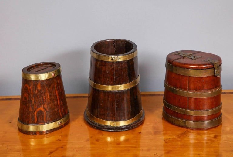 Lovely collection of three English 19th century brass bound staved vessels all of oval flaring form, the first (with two bands) an oak money bank in the form of a ship's tobacco barrel, the second (three bands) an early 19th Century Georgian