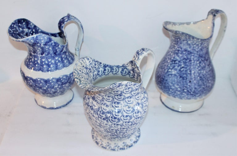 Collection of three 19th century spatter ware water pitchers in pristine condition. The shorter of the three is really quite unusual and is more of a design sponge pattern.