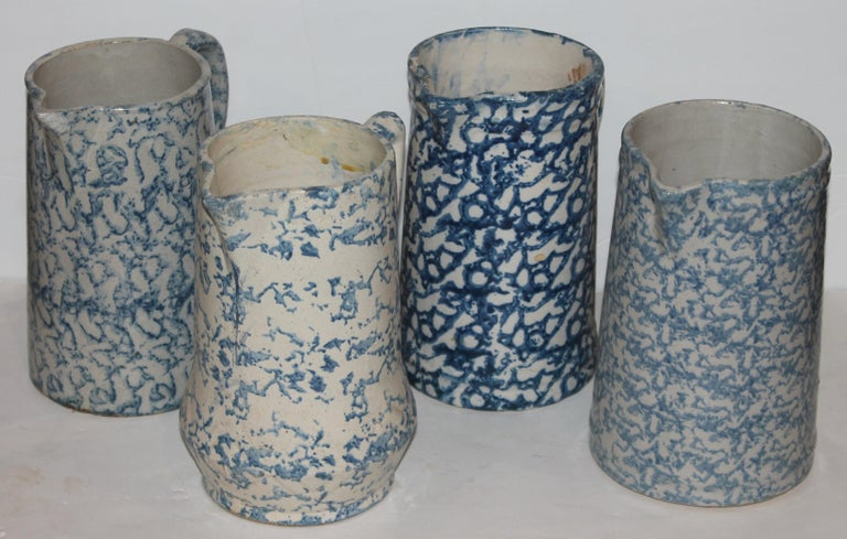 This collection of four pristine condition 19th century sponge ware pitchers and all have different colors and patterns.